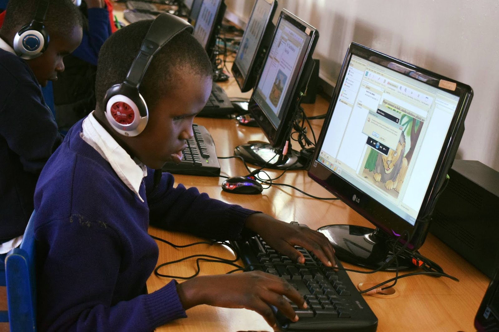 Student at Thika Primary School for the Visually Impaired using accessible ebooks on a laptop.